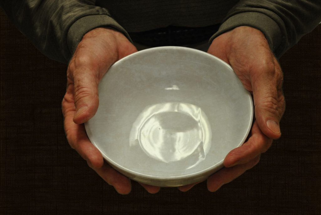 Hands holding empty white porcelain bowl